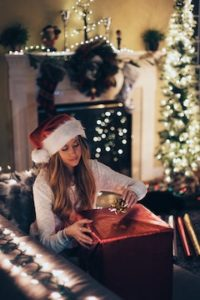 lady wearing a santa hat in front of a fireplace and christmas tree with white lights while she opens christmas presents