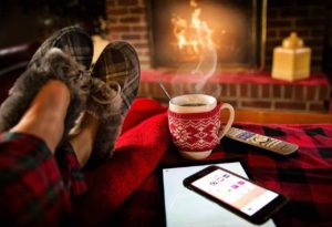 ladys feet with moccasins and a cup of coffee in front of a fire during the holidays