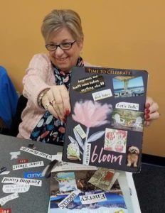 happy woman holding up a vision journal cover in a yolanda gray vision journal workshop