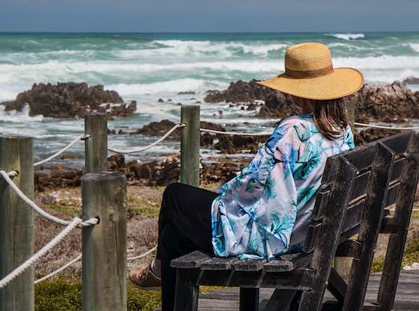 woman on bench looking at ocean blue green water