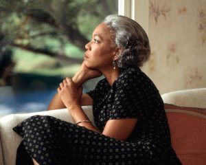 african american woman with gray hair looking into the distance pensively